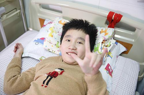 图为助养项目的受助人可儿在病床上露出乐观的笑容