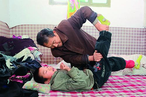 图为博浩爷爷在为项目受助人博浩做康复训练