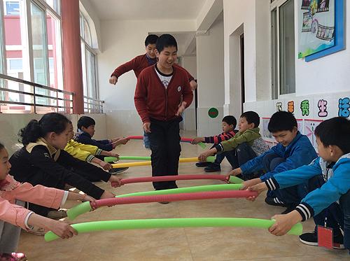 图为小雷和小宇在特教学校课间和同学做游戏