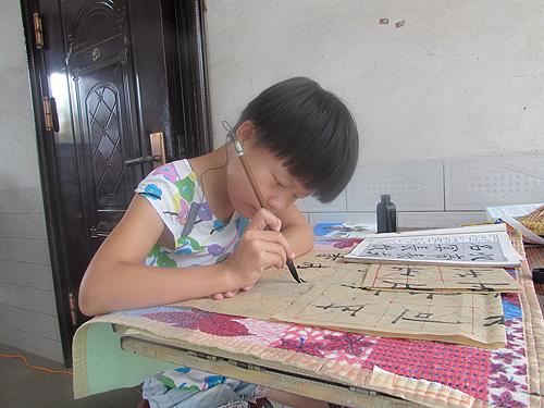 图为琪琪专心致志地练习书法