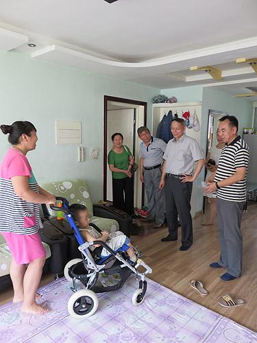 图为许小宁副理事长一行到阳光伴我行公益项目受助残疾儿童家庭了解儿童轮椅使用情况