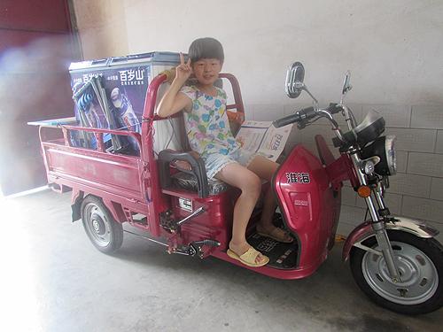 琪琪开心地坐在集善残疾儿童助养项目资助的电动三轮车上