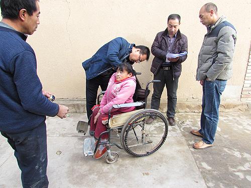 工作人員為小亮測量輪椅尺寸